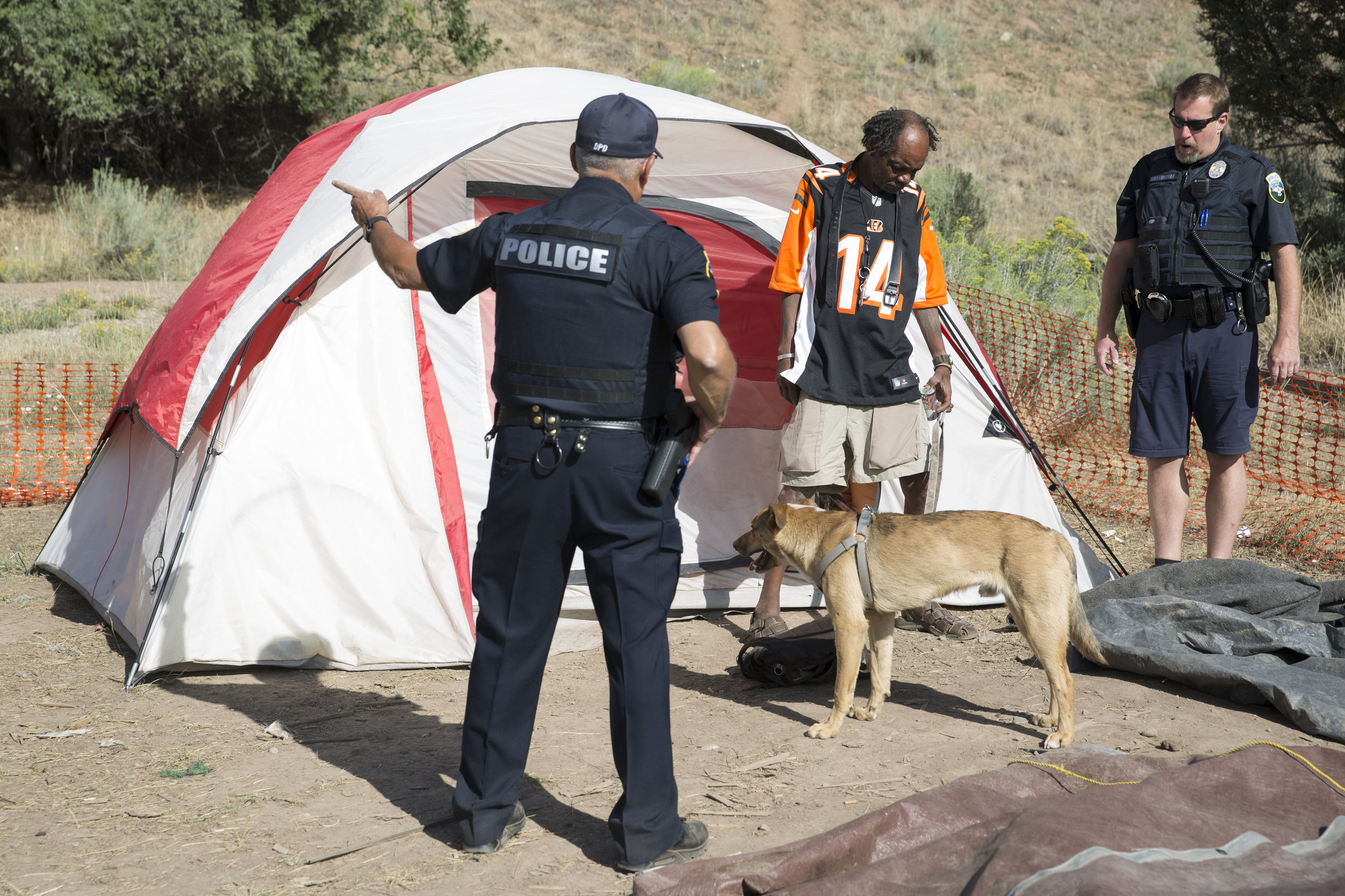 People slow to rise from a city-sanctioned homeless encampment near Durango, like Astro Aliva, center, sometimes were asked by Durango police to pack up for the day. (Scott DW Smith, Special to The Colorado Sun)