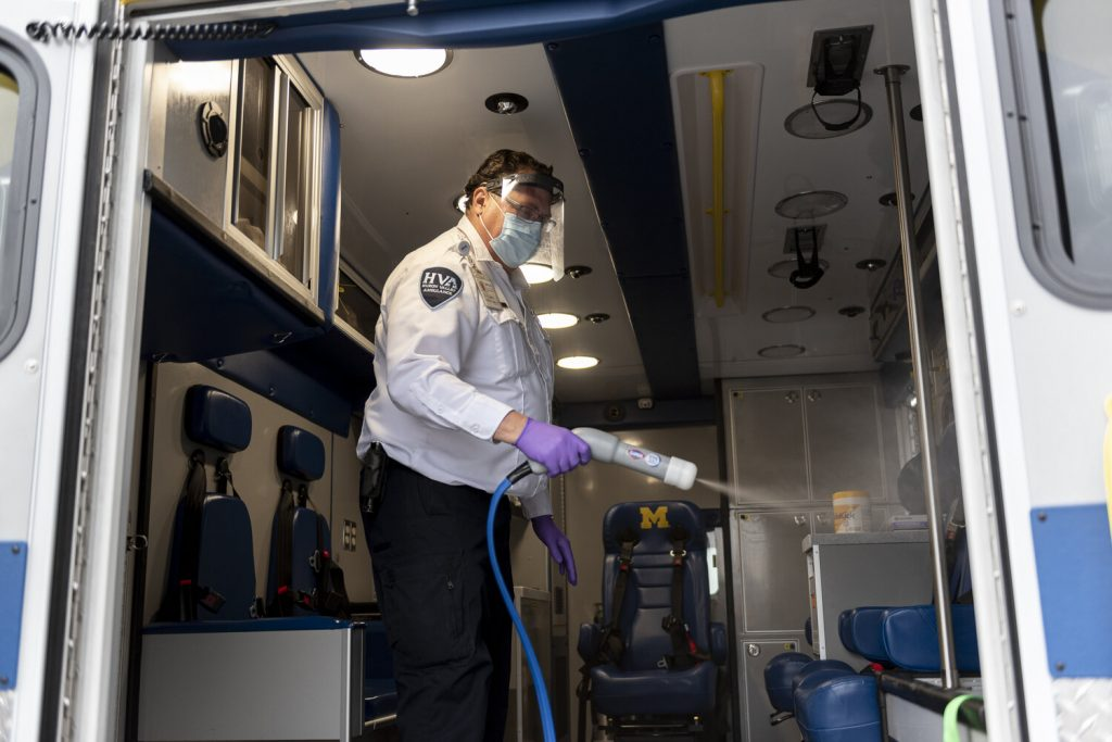 Huron Valley Ambulance Paramedic Supervisor Gary Pavelock wears a face shield donated by Operation Face Shield as he applies disinfectant to an ambulance following a Covid-19 shift in Ann Arbor, Michigan. Photo by Elliott Woods