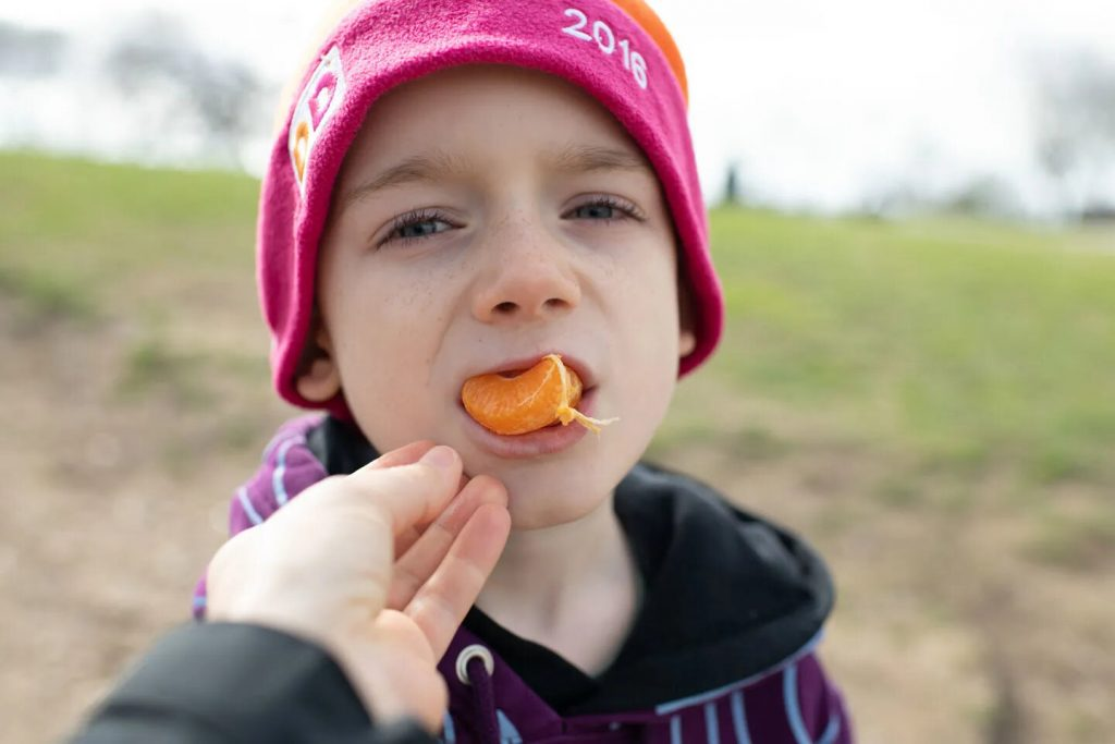 New precautions: I feed a clementine slice to my son William Murray, 7, so he doesn't have to touch it.
