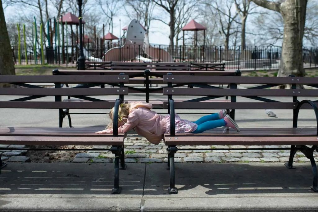 January lies on a bench in front of a closed playground in Sunset Park.