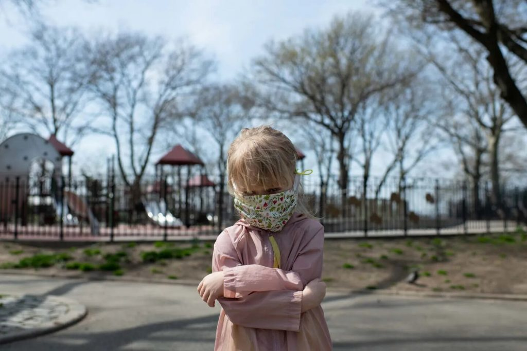 In front of a closed playground, January wears a mask my mother made her. Photo by Alice Proujansky
