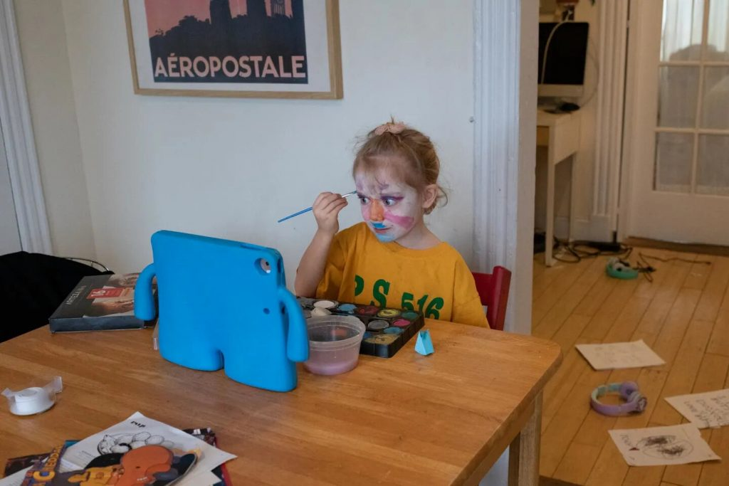 January paints her face during her Google Meet morning meeting. She avoids the meeting because she deeply misses her friends and teachers but is more engaged if she's doing something else during it.
